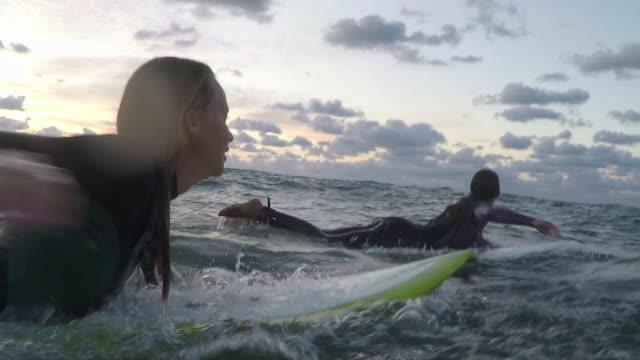 Two female surfers paddling on surfboards in the ocean at sunset in Southern France