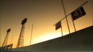 Two field light towers section signs 40 41 hanging from metal bar above stadium top wall gray to orange sky BG white sunlight behind wall Arrows...