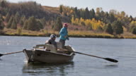 Two fly fisherpeople float and fish from a drift boat on the Snake River in Idaho