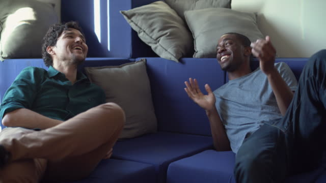 Two friends, Hispanic and Black young men, have conversation in the living room