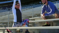 MS Two friends stretching before running stairs in stadium
