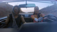 Two friends with vintage style talk and laugh in classic convertible on desert road trip.
