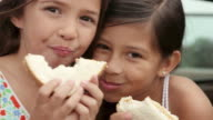 Two girls eating sandwiches
