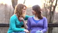 Two girls flirting in park