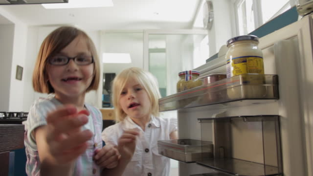 CU Two girls (6-7) grabbing eggs from fridge / London, UK