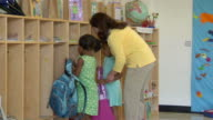 MS Two girls hanging their backpacks in cubbyholes and holding hands with their teacher in preschool classroom / San Antonio, Texas, USA
