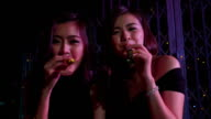 Two girls having fun with party horn blower in Slow Motion