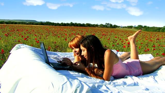 Two girls in poppy field with laptop