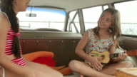 Two girls inside car, one playing guitar