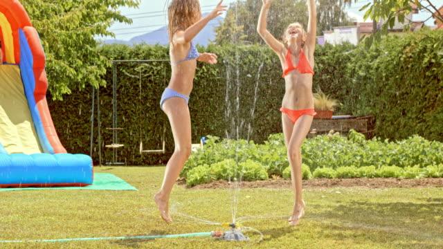 SLO MO Two girls jumping around water sprinkler