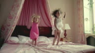 WS, Two girls (2-3, 6-7) jumping on bed, Saint Ferme, Gironde, France