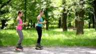 Two girls jumping with kangoo jumps shoes in the park