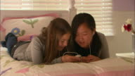 CU, Two girls (10-11) lying on bed and listening MP3 player together