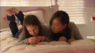 MS, Two girls (10-11) lying on bed and reading book