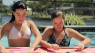 MS Two girls (14-15) on edge of swimming pool reading text messages / Cape Coral, Florida, USA