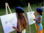 Two girls painting in the park.
