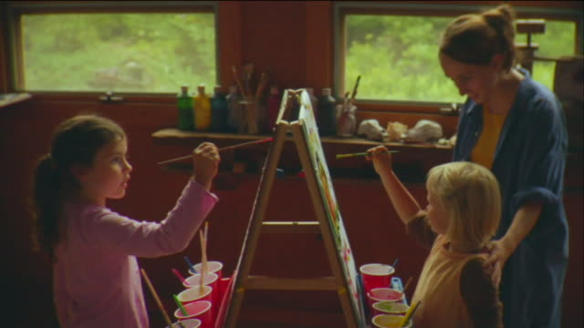 SM MS TU Two girls painting on easels while teacher watches in classroom / Vinalhaven, Maine, USA