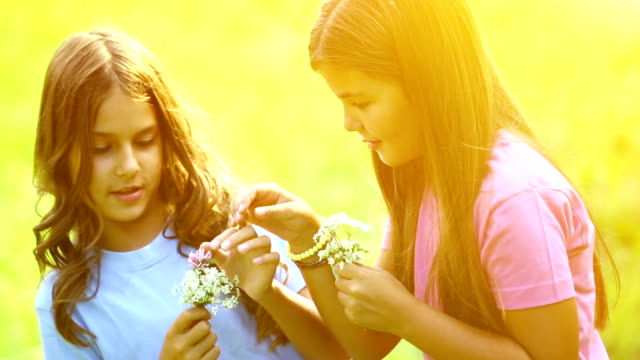 Two girls picking flowers outdoors.