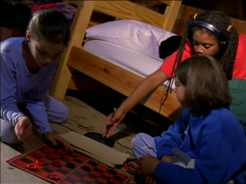 Two girls playing checkers on floor of cabin / Black girl on bunk bed showing them drawing / laugh