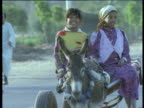 Two girls ride in cart pulled by donkey