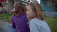 MS SLO MO. Two girls ride in red wagon as dad pulls them down neighborhood sidewalk.