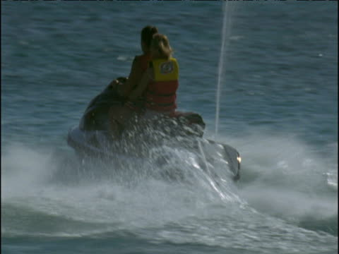 Two girls ride jet ski in sea, Barbados