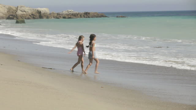 Two girls running into sea and waves