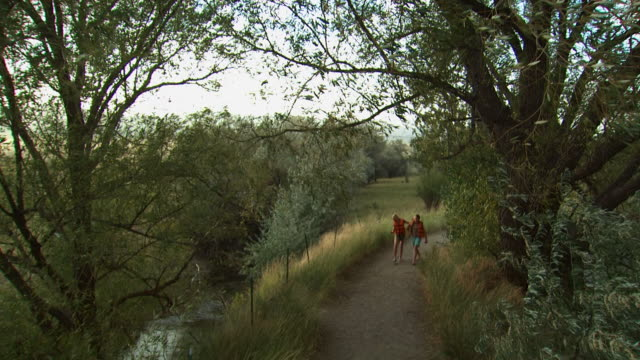 two girls skipping down a trail with life vests