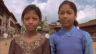 Two girls smile at camera, Baktapur, Nepal Available in HD.