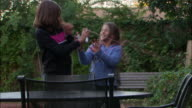 MS, PAN, Two girls (10-11) squirting party strings in garden, Los Angeles, California, USA