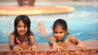 Two girls swimming in a swimming pool