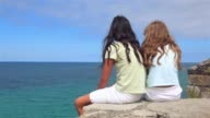 Two girls talking and laughing together sitting on the high watching the sea