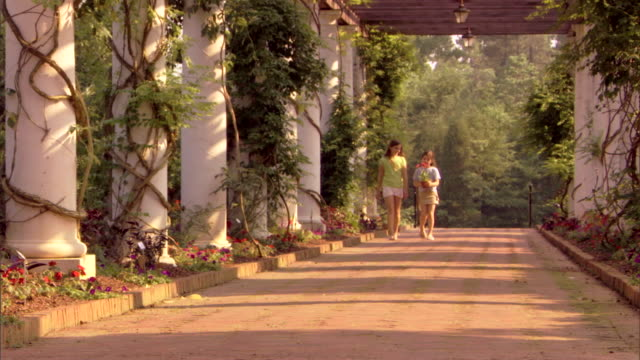 Two girls walk on a brick pathway sharing a potted flower.