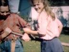 1947 two girls watch man saw tree trunk