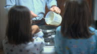 MS Two girls watching father cook pancakes on stove/ TU Father smiling/ Rome, Italy