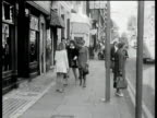 Two girls wearing sixties style mini dresses walk down street towards camera and into mod shop London