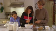 MS, Two girls (10-11) with grandmother mixing cookie dough in kitchen
