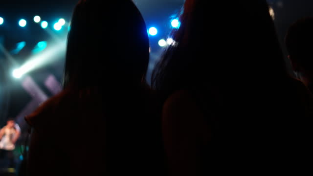 Two girls, with long hair, dancing as part of an audience at an outdoor music festival during night, with a major light display