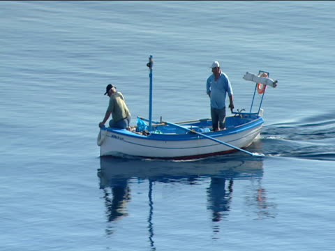 Two Greek men sail in small boat along calm sea