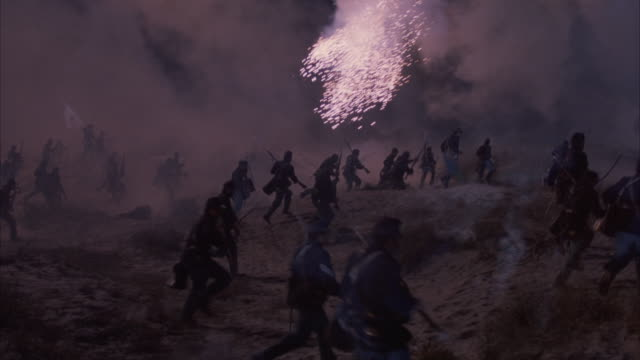 Two groups of Union soldiers run for cover to an embankment as artillery and explosions fill the air with smoke and kill several soldiers.