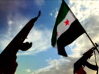 Two guns are held in the air alongside a Syrian Republic flag