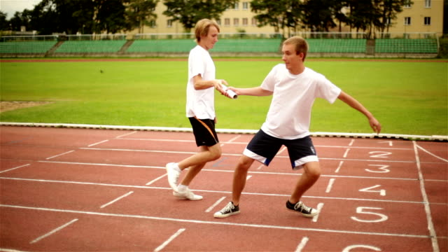 Two Hands Passing Relay Baton