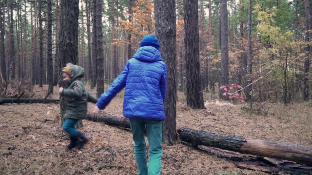 Two happy boys playing tag game in forest on autumn day