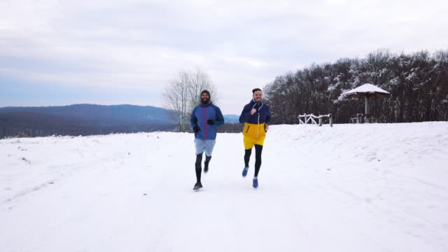 Two happy male athletes jogging on the snow in nature.