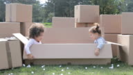 Two happy multicultural babies having fun in cardboard boxes and playing hide and seek