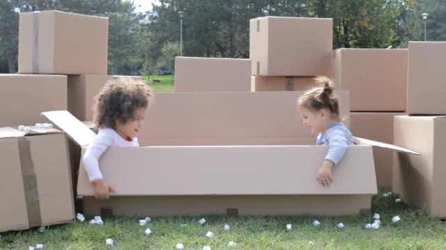 Twee gelukkige multiculturele baby's met plezier in kartonnen dozen en spelen verstoppertje