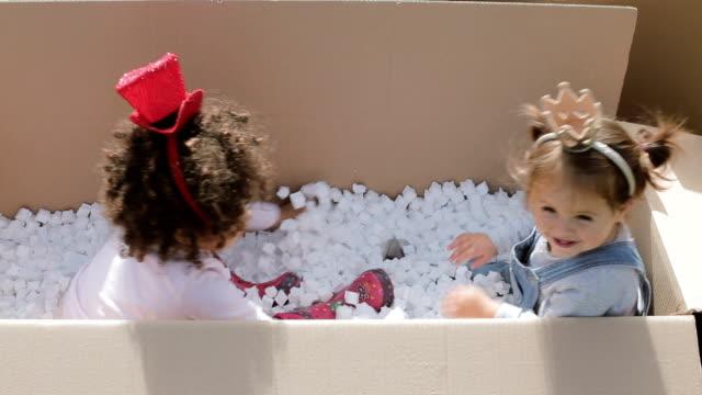 Twee gelukkige multiculturele baby's plezier in kartonnen dozen, hoofd bands, hoed en kroon