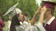 MS Two High school graduates (17-19) adjusting each other's caps and smiling at camera / Appleton, Wisconsin, USA