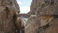 W/S. Two Hikers cross Camino del Rey Bridge in El Chorro, Spain.