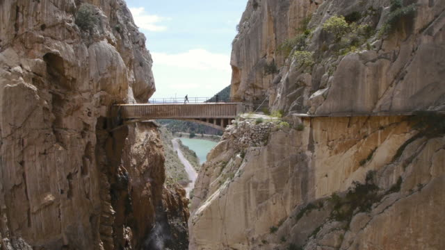 W/S. Two Hikers cross Camino del Rey Bridge in El Chorro, Spain.